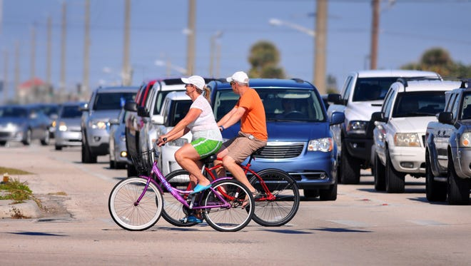 A couple crosses State Road A1A at Shepard Drive in Cocoa Beach on their bikes.