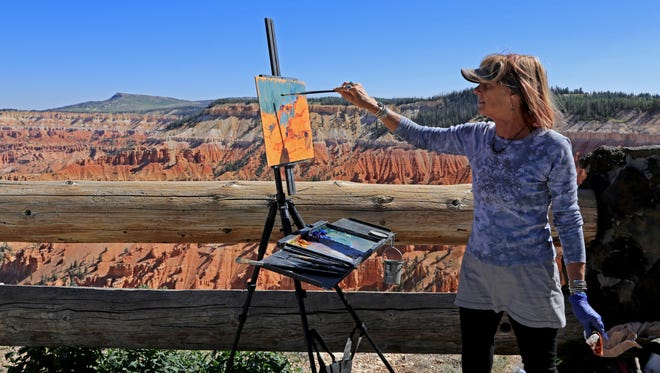 "Susiehyer, of Evergreen, Colo., paints during the ""Chasing Light"" plein air event Monday at Cedar Breaks National Monument."
