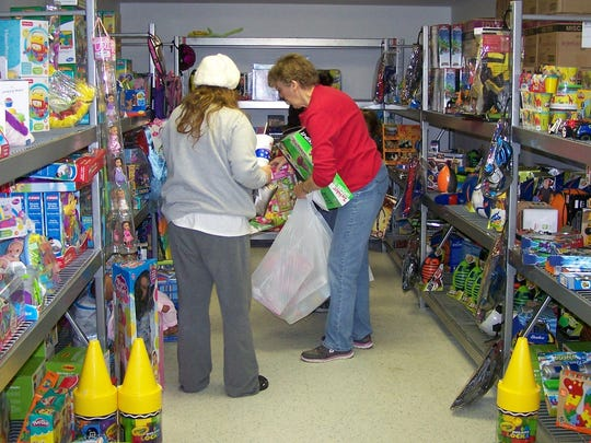 Volunteer Judy Sullivan helps a customer pick out toys for her children during the 2016 Christmas Store.