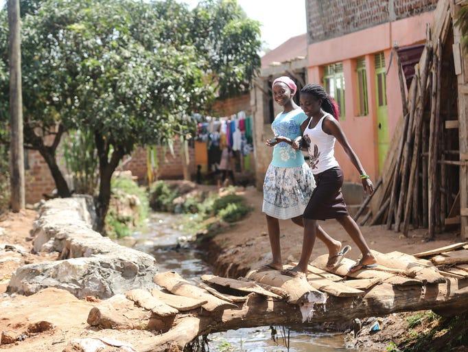 Natalia Peni, 19, on right, walks through her neighborhood