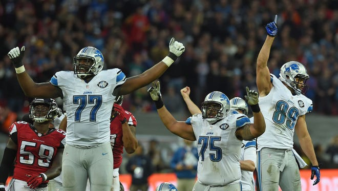 Detroit Lions players, including Cornelius Lucas (77), celebrate after Matt Prater kicked the game-winning field goal against the Atlanta Falcons at Wembley Stadium in London, Sunday, Oct. 26, 2014.