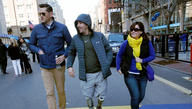 Boston Marathon bombing survivor Jeff Bauman, center, walks over the marathon finish line on the third anniversary of the bombings, Friday, April 15, 2016, in Boston. One of the bombers, Dzhokhar Tsarnaev, was sentenced to death in June. His brother, Tamerlan, died in a gunfight with police in the days after the attack.  (AP Photo/Michael Dwyer)