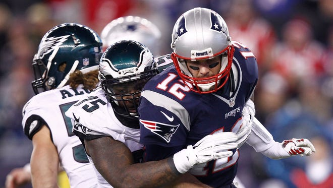 New England Patriots quarterback Tom Brady (12) is tackled by Philadelphia Eagles defensive end Vinny Curry (back) during the second half at Gillette Stadium.
