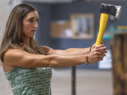 Melissa Blevins takes aim at the target with her hand ax at Bull's Eye Axe Throwing in Lansing. The business has a competitive league that includes 11 women.
