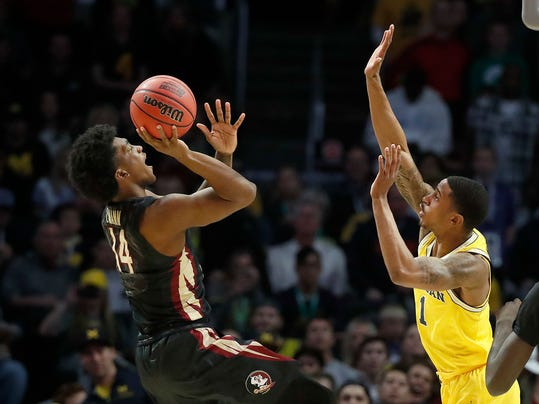 Florida State guard Terance Mann, left, shoots against Michigan guard Charles Matthews during the first half of an NCAA men's college basketball tournament regional final Saturday, March 24, 2018, in Los Angeles. (AP Photo/Jae Hong)