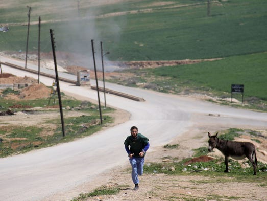 A Syrian medic runs for cover during the air strikes