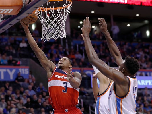 Washington Wizards guard Bradley Beal, left, goes to the basket in front of Oklahoma City Thunder forward Andre Roberson, back and forward Jerami Grant, right, during the first half of an NBA basketball game in Oklahoma City, Wednesday, Nov. 30, 2016. (AP Photo/Alonzo Adams)