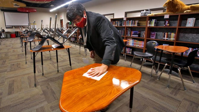 Jeff Ziegler, Dean of Academics, wipes desks down after school at Pinnacle Classical Academy on Monday. High school students recently returned to in-person learning five days a week.