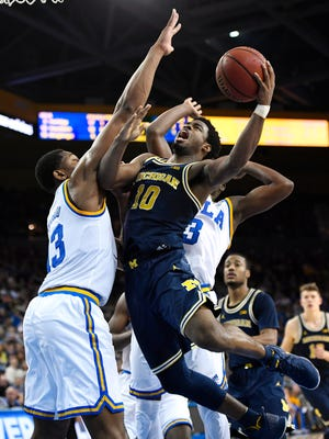 Michigan guard Derrick Walton Jr., right, shoots as UCLA forward Ike Anigbogu defends during the second half of U-M's 102-84 loss Saturday in Los Angeles.