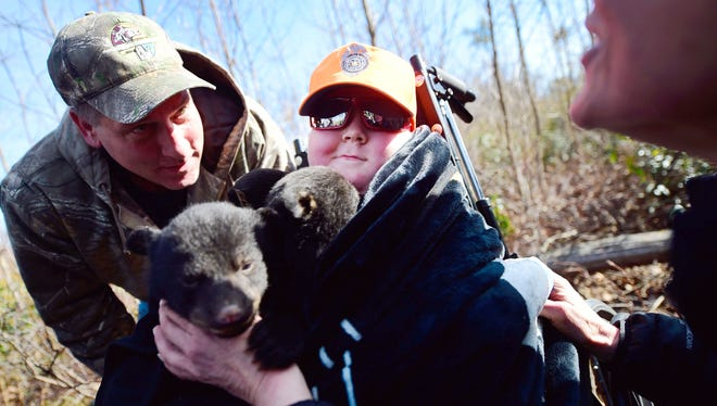 Ayden Zeigler-Kohler, 10, of Springettsbury Township, Pa., smiles in early March 2017, as he cuddles with three bear cubs in the Sproul State Forrest in Noyse Township, Pa. Ayden and his father, Bill Kohler, left, were invited to hold the cubs who were being checked on as a part of a Pennsylvania Game Commission study after a wildlife conservation officer read that Ayden was dying from a rare childhood cancer.