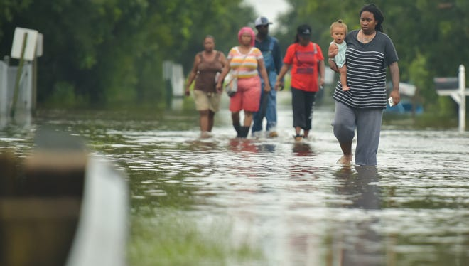 Tearra Mouton wades through flood waters as heavy rain causes flash flooding in Carencro, LA.- Thursday, June 29, 2017.
