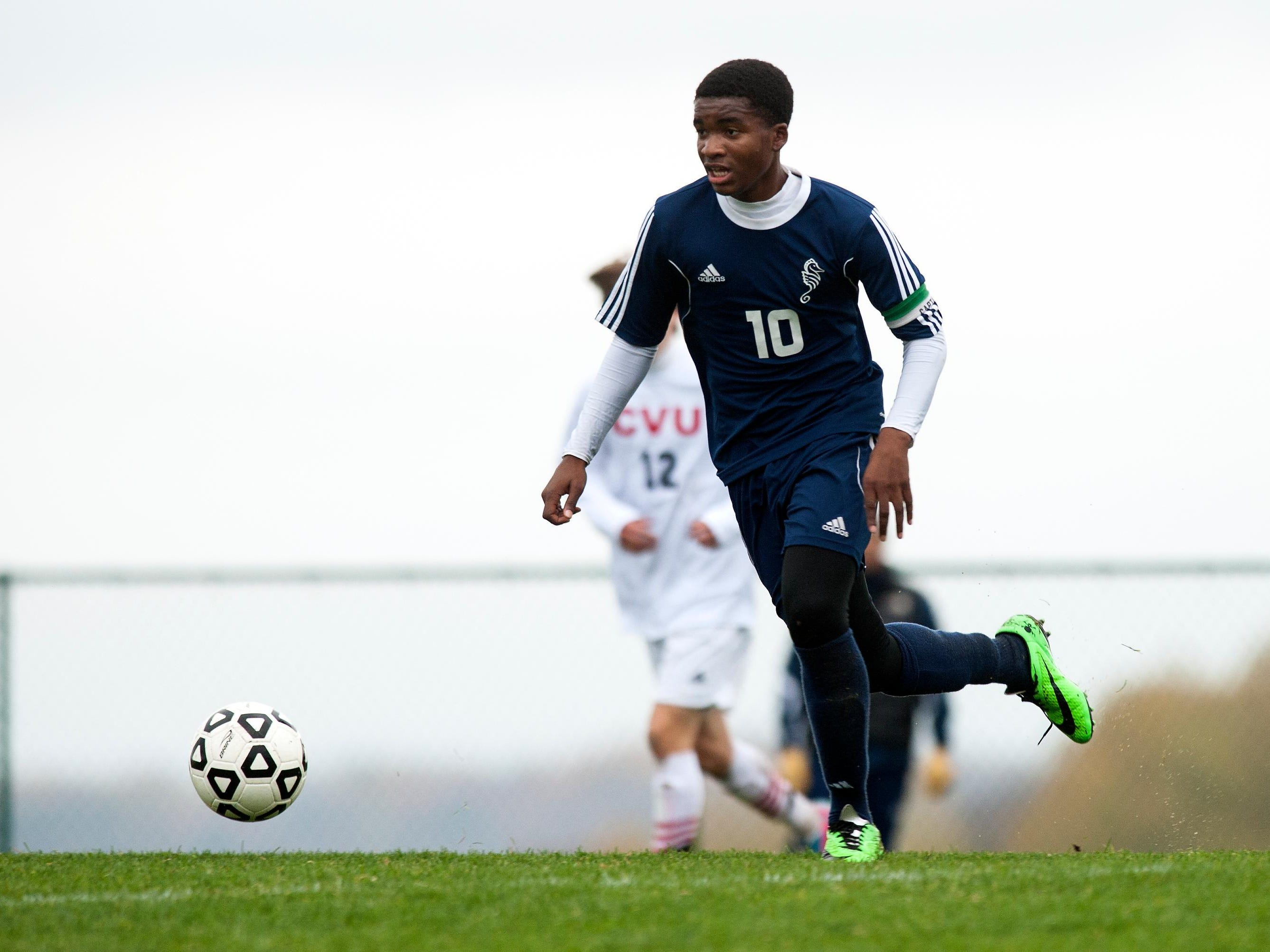 Burlington's Peter Makuni (10) runs down the field with the ball during the boys soccer playoff game between the Burlington Sea Horses and the Champlain Valley Union Redhawks at CVU High School on Wednesday afternoon October 22, 2014 in Hinesburg, Vermont. (BRIAN JENKINS, for the Free Press)