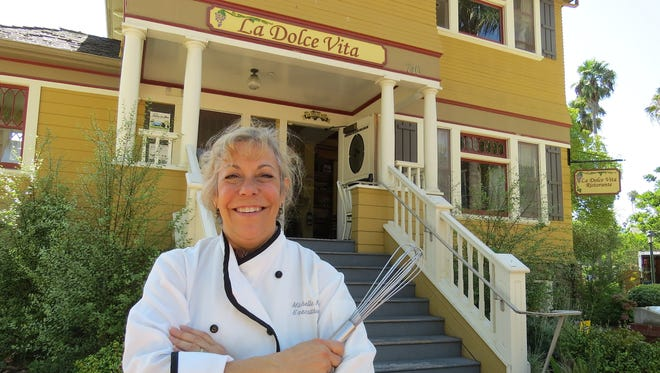 "Michelle Kenney, co-owner and executive chef of La Dolce Vita Ristorante, poses in front of the restaurant's location in Oxnard's Heritage Square. Kenney jokes that her kitchen inside the historic Laurent/McGrath House is ""smaller than a small bedroom in a new condo."""