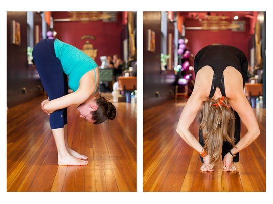Forward fold, demonstrated by Amy Sipe, left, and Evy Doherty, instructors for House of Yoga and the York Branch YMCA.
