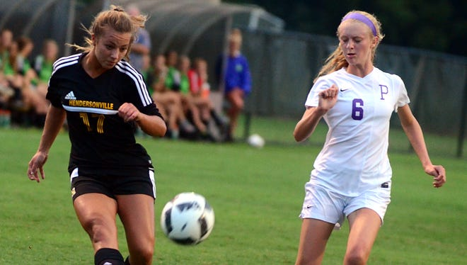 Hendersonville High junior Katie Easter takes a shot as Portland junior Ele Loza defends during Thursday's match.