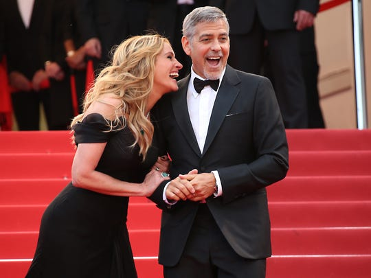Julia Roberts tells George Clooney a little secret on the Cannes red carpet Thursday night.