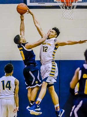 Josh Horford ,12, of Grand Ledge blocks a shot attempt by Isaac Ries of Eastern but gets a hand in the face from Ries during their Class A district semifinal game Wednesday March 9, 2016 in East Lansing. KEVIN W. FOWLER PHOTO