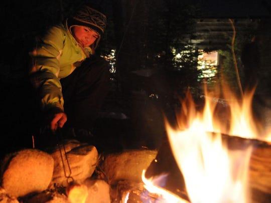 Mya Ploor roasts marshmallows over an open fire during
