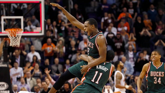 The Milwaukee Bucks' Khris Middleton is picked up by teammate Brandon Knight (11) after scoring the game-winning basket against the Phoenix Suns on Monday night in Phoenix. The Bucks won 96-94.