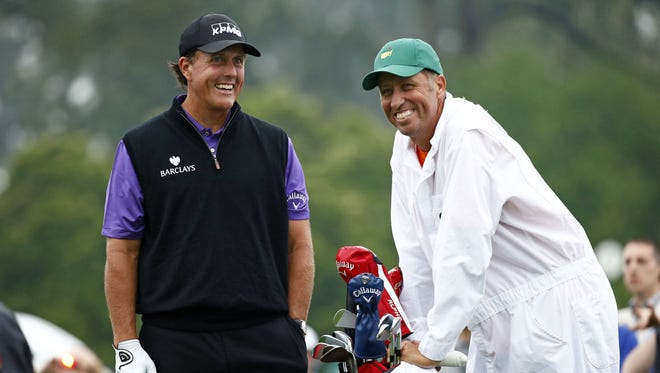 "Phil Mickelson and caddie Jim ""Bones"" Mackay wait to tee off on the 1st hole during a practice round for the Masters in 2015."