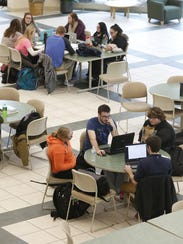 Students work in the commons area at the University