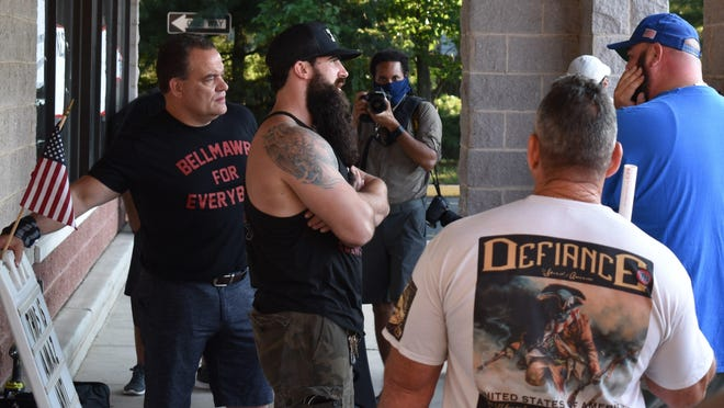 Supporters talk to Atilis Gym partners Ian Smith, center, and Frank Trumbetti, left, outside the Bellmawr business on Saturday.