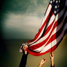 Hands reach for an American flag