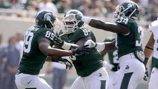 MSU defender Shilique Calhoun, Lawrence Thomas and Taiwan Jones, left to right, celebrate a defensive stop against Eastern Michigan last week. This trio is could use a tone-setting, dominating performance against Wyoming.