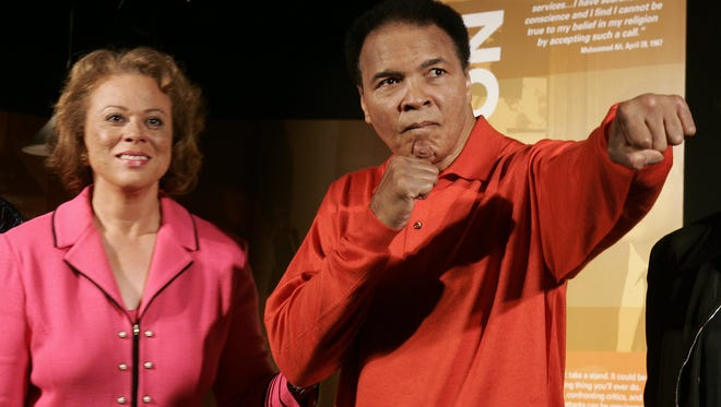 Muhammad Ali (R) strikes a boxing pose with wife Lonnie (L) at the Muhammad Ali Center 18 November, 2005 in Louisville, KY before the grand opening of the new center. Directors declare the USD 75 million center more than a museum, although many exhibits will pay homage to the life and career of the famed fighter, whose refusal to be drafted into fighting in the Vietnam War cost him his title. Designed to be a global gathering place for sharing the legacy and values of the heavyweight boxing legend, the Muhammad Ali Center opens with ceremonies 20 November 2005.  AFP PHOTO/JEFF HAYNES (Photo credit should read JEFF HAYNES/AFP/Getty Images)