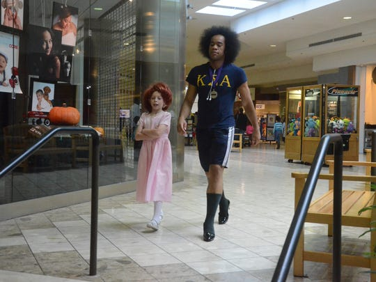 Jarrell Brackett, 27, of Olivet College walks in high heels with Izaak Oldenburg, 9, of Battle Creek during a fundraising event for SAFE Place earlier this year.