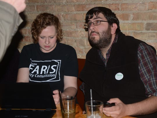 Kaytee Faris checks results with a supporter, Nathan Grajek.