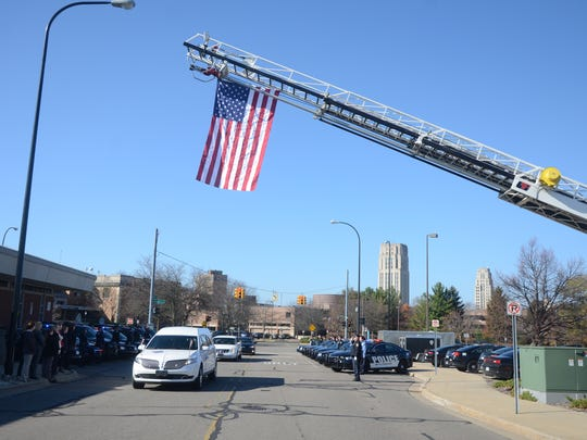 The hearse with the body of retired detective Al Tolf, Sr. passes the Battle Creek Police Department Monday afternoon.