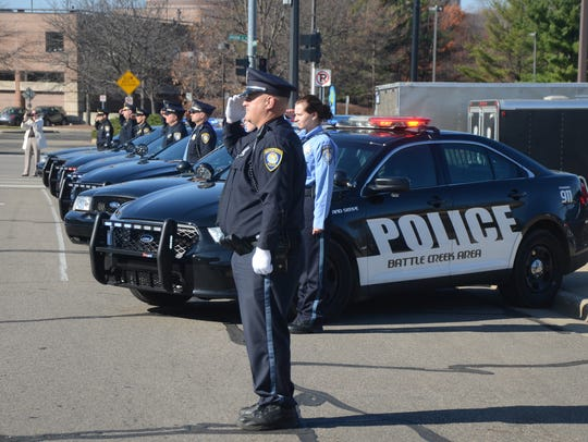 Officers salute the funeral procession of Al Tolf,