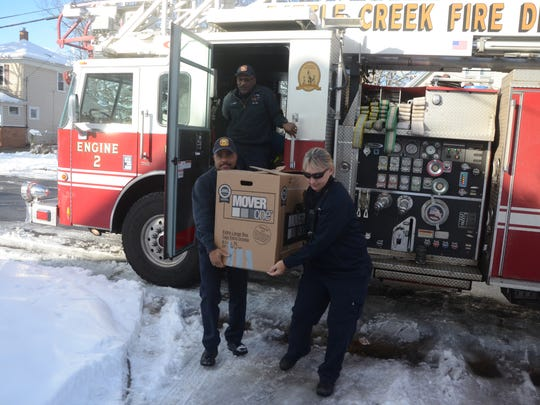 Lt. Jeannell Justin and Battle Creek Firefighters Calvin Hardin, front and Carl Turner deliver Thanksgiving food Sunday.