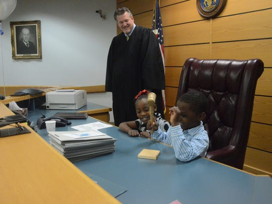 Chief Probate Judge Michael Jaconette invited Oliver Bond and his sister, Onysti Mitchell, 5, to the bench to try the gavel before Adoption Day began.