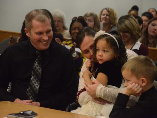 Carl and Jill Damon with their daughter, Ava, after her adoption, and one of their three sons, Heath, 7.