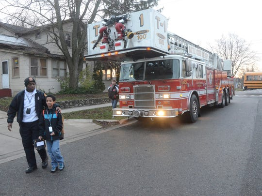 Fire Marshal Quincy Jones walks with Tayshaun Twigg-Jackson after his ride to school in a fire truck.