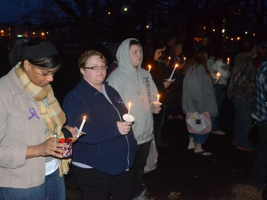 Those attending the vigil wore purple ribbons and held