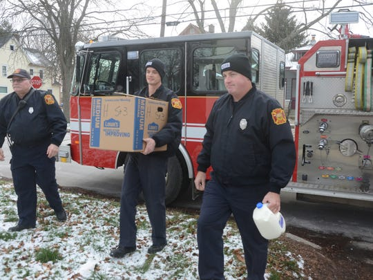 A fire crew from the Cliff Street station, from left, Lt.. Brian Bartzen, Michael Tobin and Joe Shanks, deliver a box of food Sunday.