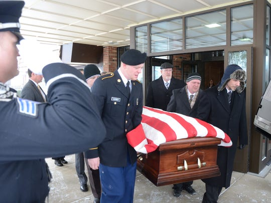 Moving past a Battle Creek Police Department Honor Guard, pallbearers place the casket of Dyke Eutsey into a hearse.