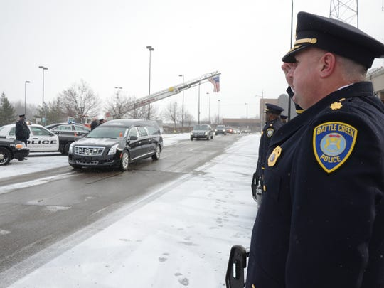 Major Jim Grafton joins other members of the department saluting the hearse with the body of retired Sgt. Dyke Eutsey.