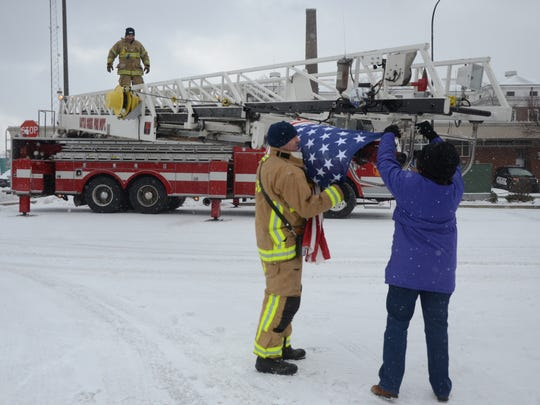 After the procession passed the American flag is removed from the top of the fire department ladder truck.