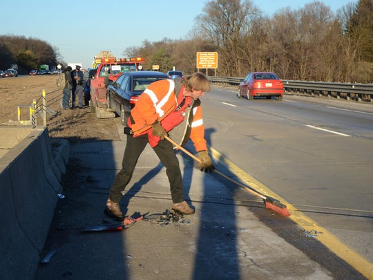 A wrecker driver clears debris after the accident on I-94.