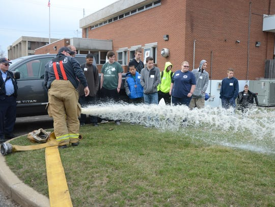 Battle Creek firefighters show a group of students