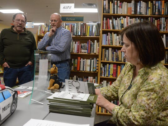 "As Suzanne Berube Rorhus signs copies of ""Cuffed,"" retired Battle Creek officer Bill Broderick, left, talks with Bill Howe."
