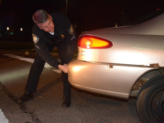 Sgt. Mike Wood removes an improper license plate from