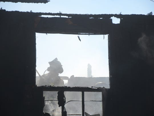 A firefighter in the one of the fire damaged third