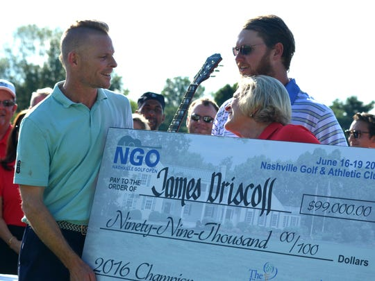 James Driscoll, left, accepts a $99,000 check for winning