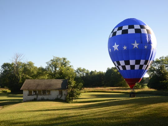 Joe Heartsill lands his balloon on property on Division Drive south of Battle Creek on Wednesday morning.