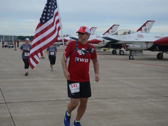 Greg Hacke of Terrytown, N.Y. carries an American Flag